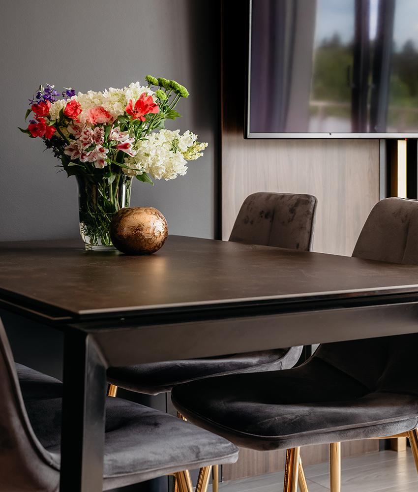 Stół w salonie oraz krzesła ze złotymi nóżkami